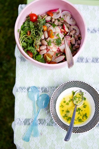Summer Salad in a Pink Serving Bowl with a Bowl of Dressing