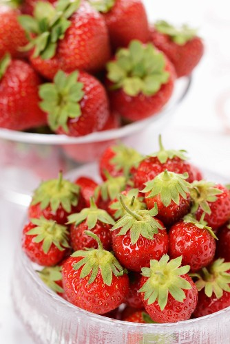 Fresh strawberries in glass bowls