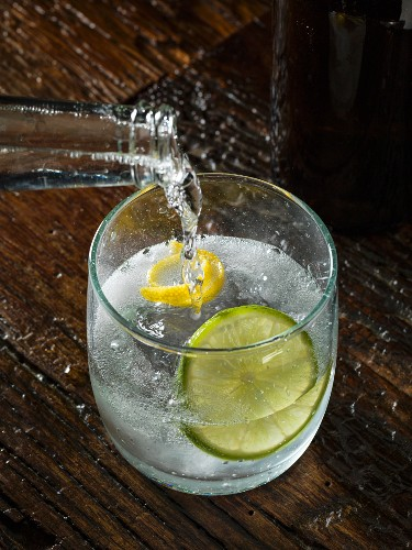 Tonic water being poured into a glass of gin