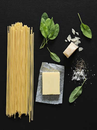 An arrangement of spaghetti, butter, sage and Parmesan cheese