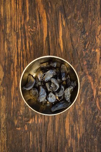 Black fermented garlic in a golden bowl