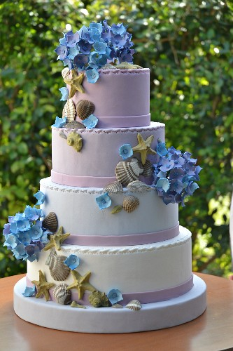 A multi-tiered wedding cake decorated with shells and hydrangeas