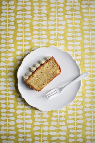 A slice of lemon and poppyseed cake with cream cheese frosting on white plate with a fork