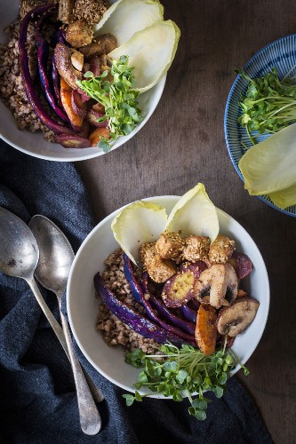 Buchweizen, Gemüse, Sesam-Tofu und Kresse in Schale auf Holztisch mit Leinentuch und Vintage-Löffeln