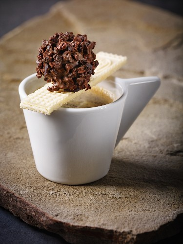 A homemade nougat truffle in dark chocolate with cocoa bean splinters on a cup of espresso with a wafer