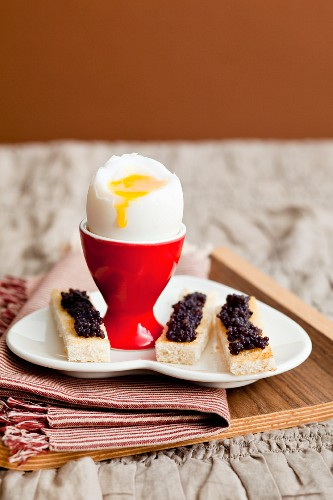 Soft boiled egg with caviar on 'soldiers' (thin toast slices)