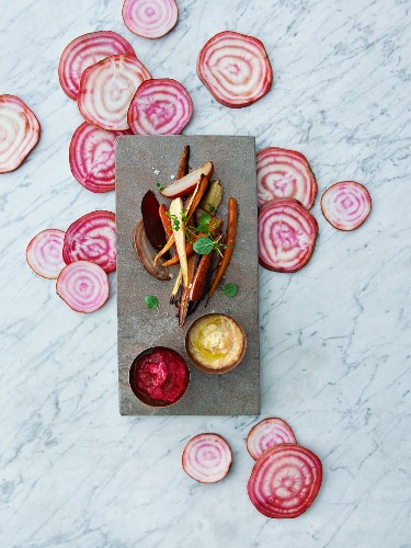 Baked root vegetables with red and yellow hummus