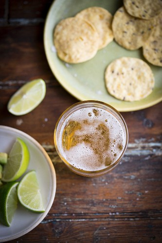 A glass of lager, limes and corn chips