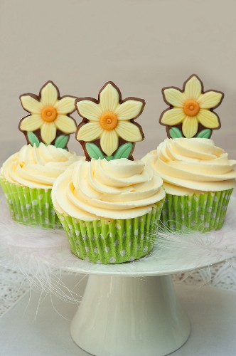 Easter cupcakes on a white cake stand, decorated with feathers and chocolate spring daffodil flowers on white lace