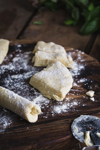 Ricotta gnocchi on a wooden board being rolled