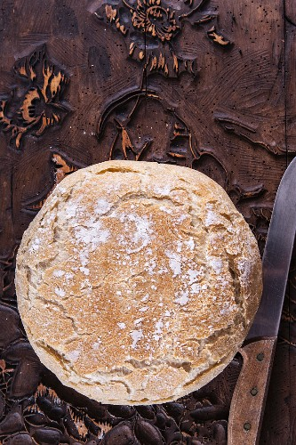 Wheat bread baked in a pot: a whole loaf on a wooden surface (top view)