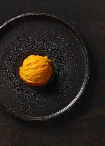 A scoop of pumpkin ice cream with black sesame seeds