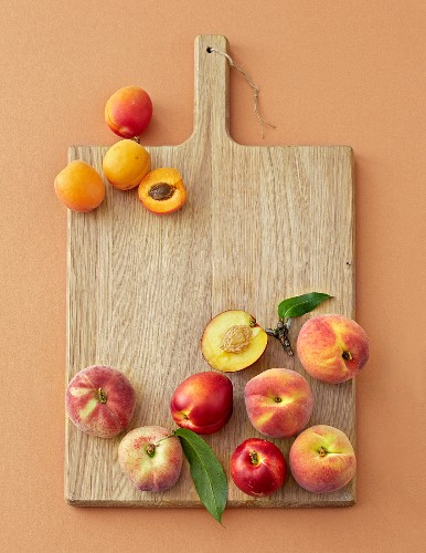 Peaches, nectarines and apricots on a wooden board