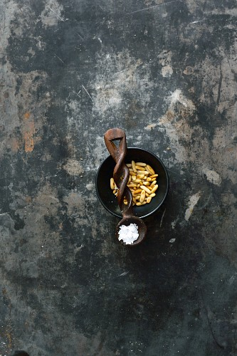 Roasted pine nuts in a bowl and salt crystals on a wooden spoon