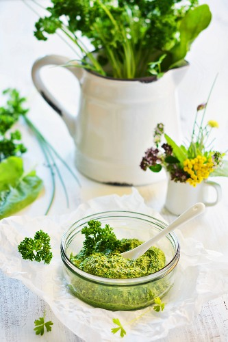 Mixed herb pesto in a glass bowl, with a jug of herbs in the background