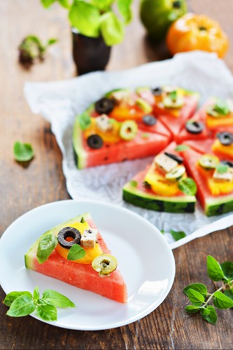 A slice of melon garnished like a pizza with tomatoes, tofu, olives and fresh herbs