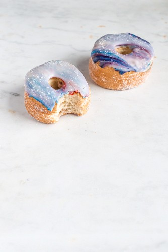 Two galaxy croissant doughnuts with marble glaze, a bite missing