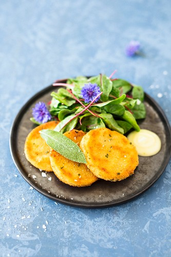Baked cabbage slices with mangold salad and edible flowers