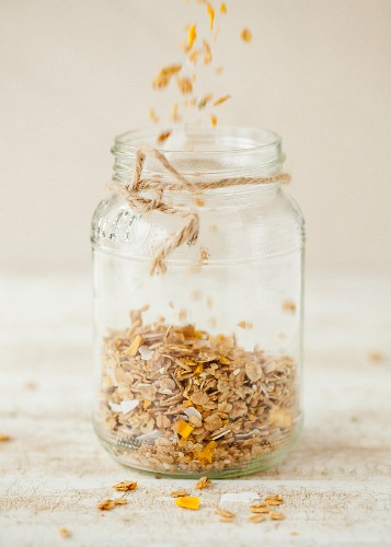 Homemade Granola Being Poured Into a Jar