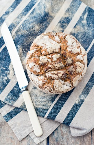 A loaf of homemade sourdough bread on a cloth next to a bag of flour and a knife