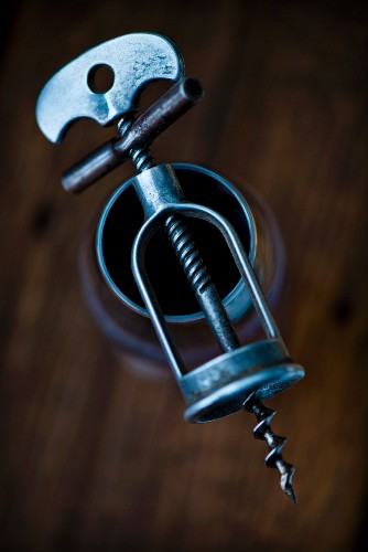 An antique corkscrew on top of a glass of red wine