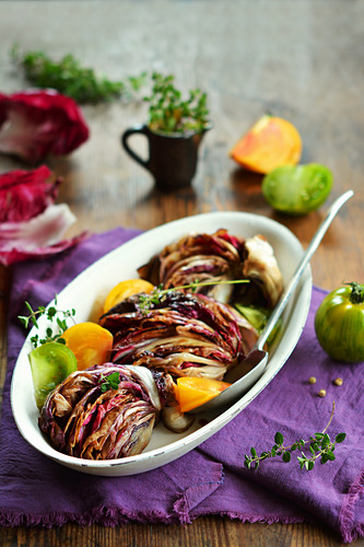 Fried radicchio with fresh tomatoes and herbs in a bowl
