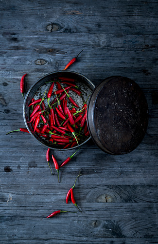 Fresh red chilli peppers in a metal tin