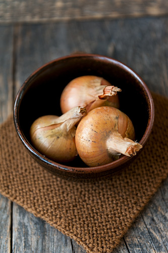Three onions in a brown bowl