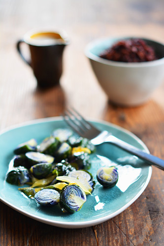 Fried Brussels sprouts on a ceramic plate in front of a bowl of wild rice and a jug of gravy
