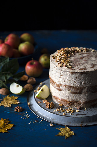 Apple layer cake with walnut frosting, on a dark surface