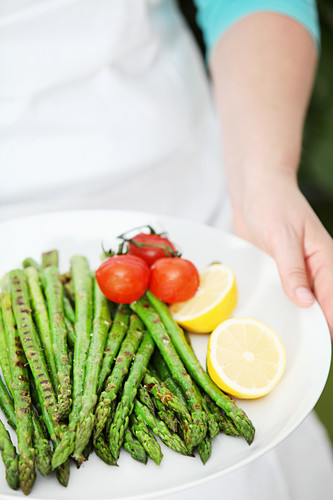 Woman holds plate with grilled green asparagus