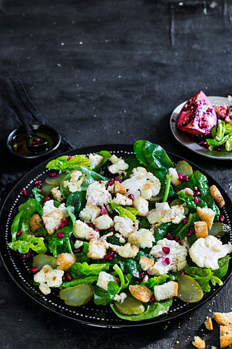 Warmer Blumenkohlsalat mit Essiggurken, Croutons und Granatapfelkernen