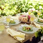 Gedeckter Tisch mit Wein und Jacobsmuscheln auf Salatteller