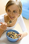 Young woman eating muesli with fresh blueberries