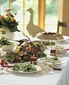 Herbstlich gedeckter Tisch mit Suppe, Salat, Zinnien-Girlande