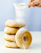 Dusting giant lemon doughnuts with icing sugar