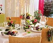Weihnachtstisch mit Rosen, Kiefer, Efeu und Baumschmuck
