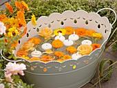 Ringelblumen, Rosen, Gräser und Schwimmkerzen in Metallwanne