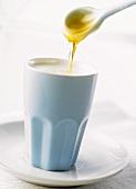 Honey running from spoon into hot milk