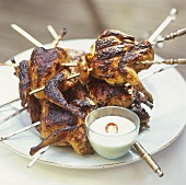 Grilled skewered quail with tahini and lemon sauce