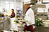 Koch trägt mehrere Salatteller