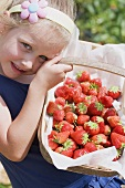 A girl in a garden holding a basket of strawberries