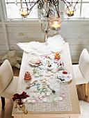 Blick auf einen gedeckten Weihnachtstisch mit Engelsflügeln, Weihnachtsgebäck und festlicher Weihnachtsdekoration