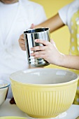 Children sieving flour into a mixing bowl
