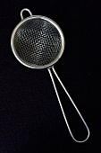 Small sieve against black background