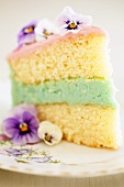 Piece of cake with coloured filling and pansies