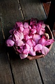 A bowl of purple lotus flowers on a wooden floor