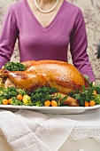 Woman holding a stuffed roast turkey on a platter