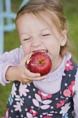 A girl biting into an apple