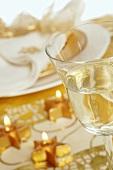 Goldener Weihnachtstisch mit Sternkerzen und Weinglas